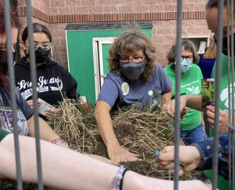 Elmhurst Garden Club member Julia Lamb shows students how to break up the soil and water when planting lettuce and other vegetables in a raised-bed garden. You want to put your tallest plants in the back, so they dont shade the others when they grow big, Lamb said.