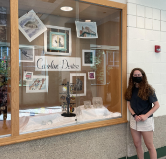 """Senior Caroline Dorion stands in front of her AP art exhibit in the hallway next to the senior courtyard. """"My favorite [piece] is probably the homeless man on the cardboard or the self portrait in the beam,"""" Dorion said. """"I just really like the detail in the homeless man and the message that it brings across with it being on cardboard, and for the self-portrait, that was kind of fun because it's not really what you would expect to see."""""""