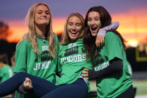 Junior girls celebrate a win at the annual Girls Flag Football game against the senior girls. The flag football game is a vital part of the Homecoming traditions. Pictured left to right: Mathilde Cronin, Megan Brandt and Ashley Simonis.